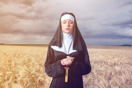 sotana: Joven serio monja con cruz sobre fondo de campo de trigo Foto de archivo