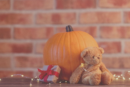 Autumn pumpkin with Fairy Lights at Halloween holiday on brick background Stock Photo