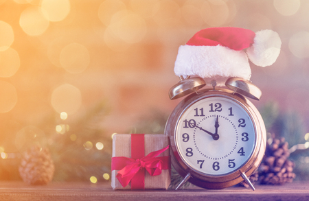 boxing day: Retro alarm clock with Santa Claus hat with Christmas Fairy Ligths at background Stock Photo