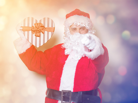 Funny Santa Claus holding heart shape gift on yellow background