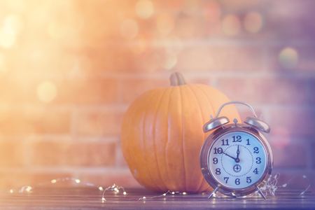 Autumn pumpkin with Fairy Lights and alarm clock at Halloween holiday on brick background