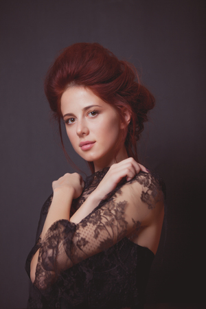 Young redhead woman in black dress on grey background