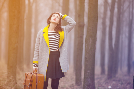 Young woman with suitcase at outdoor countryside. Autumn season