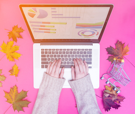 Female hands typing at laptop computer with graphic projects near shopping cart and autumn maple leaves around at pink background
