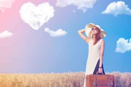 Redhead girl with suitcase at countryside road near wheat field with heart shape clouds at background