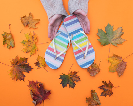 Above view at hands holding flip flops sandale with autumn maple leaves around it Stock Photo