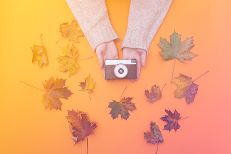 Above view at female hands holding vintage camera with autumn maple leaves around it