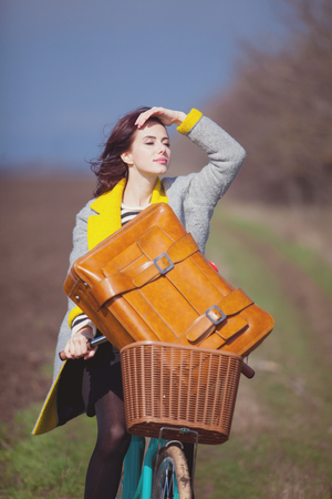 Young woman with suitcase and bike at outdoor countryside. Autumn season