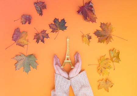 Above view at hands holding Eiffel Tower toy with autumn maple leaves around it