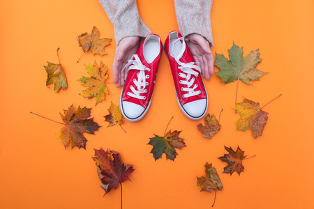 Above view at hands holding red gumshoes with autumn maple leaves around it