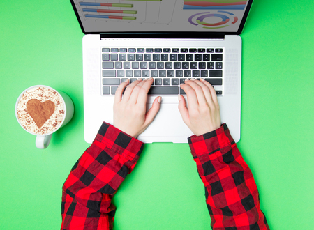 Freelancer woman hands with cup of coffee and laptop on green background Stock Photo