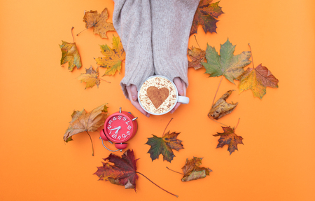 Above view at hands holding cup of cappuccino with heart shape and autumn maple leaves around it Stock Photo