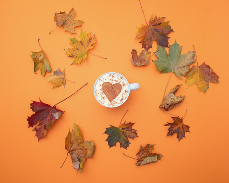 Above view at cup of cappuccino with heart shape and autumn maple leaves around it Stock Photo