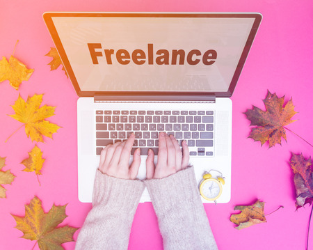 Freelance businesswoman hands typing at laptop computer with autumn maple leaves around at pink background