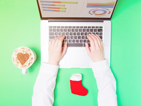Female hands and laptop with Christmas sock on green background