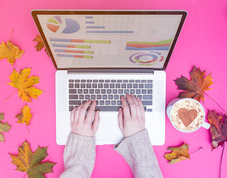 businesswoman hands typing at laptop computer with autumn maple leaves around at pink background