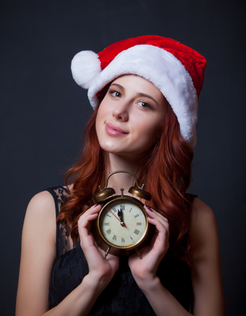 Portrait of young redhead woman in Santa Claus hat with alarm clock on grey background