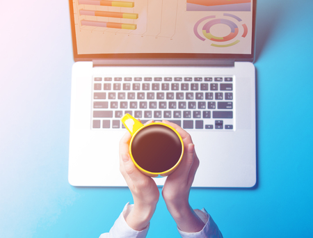 Female businesswoman hands with laptop and cup of coffee on blue background