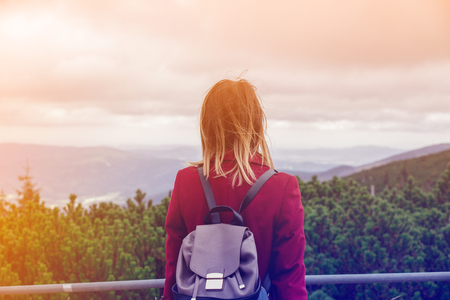Young redhead woman in red coat stay at outdoor and looking at mountains. Autumn season