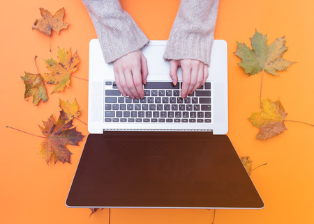 Female hands typing at laptop computer with autumn maple leaves aroung at orange background