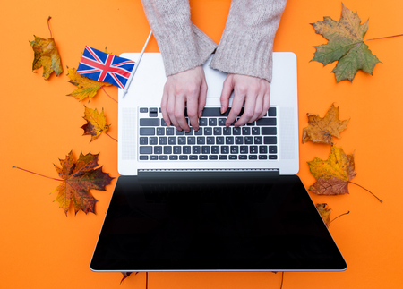 Female hands typing at laptop computer near Great Britain flag with autumn maple leaves aroung at orange background Stock Photo