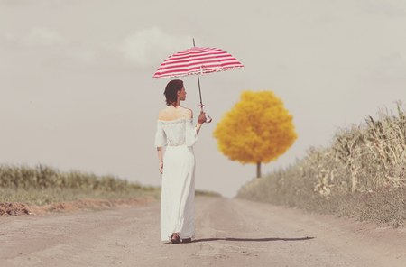 photo of the beautiful young woman with umbrella walking on the road