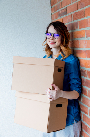 moving box: young redhead woman in jeans shirt standing on brick wall with moving boxes. European ethnicity