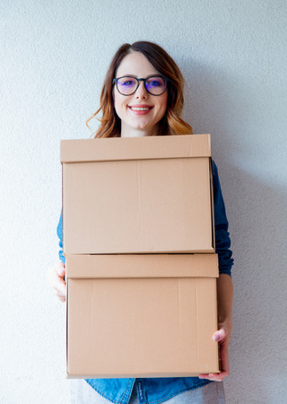 moving box: young redhead woman in jeans shirt standing on white wall with moving boxes. European ethnicity