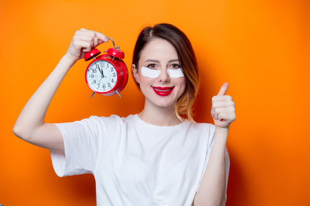 Woman using eye patch for her eyes and holding alarm clock on orange background isolated. Portrait of natural  and true female as usually they are looks like