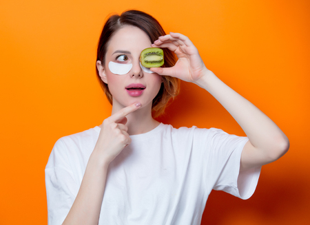 Woman using eye patch for her eyes and holding kiwi on orange background isolated. Portrait of natural and true female as usually they are looks like