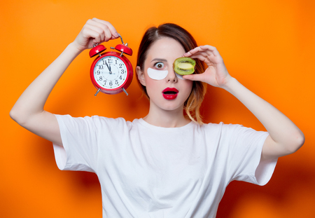Woman using eye patch for her eyes on orange background isolated. Portrait of natural  and true female as usually they are looks like Stock Photo