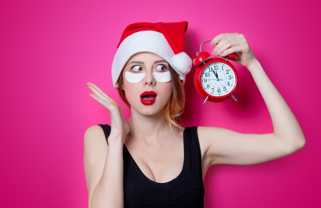 Woman using eye patch for her eyes in Santa Claus hat with alarm clock on pink background isolated. Portrait of natural  and true female as usually they are looks like
