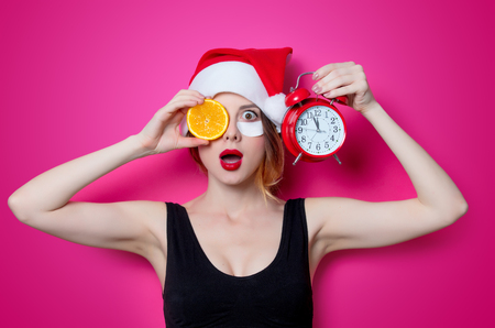 Woman using eye patch for her eyes in Santa Claus hat with orange and alarm clock on pink background isolated. Portrait of natural  and true female as usually they are looks like