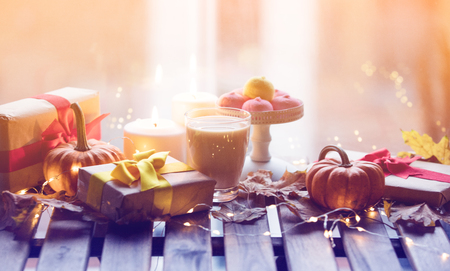 cup of coffee or tea near a pumpkin, gifts and candles with maple leaves and Fairy Lights  around on a wooden table near a window in rainy day. Autumn season image Stok Fotoğraf
