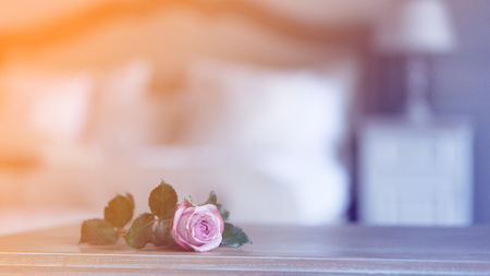 pink rose on wooden table with Fairy Ligths in bedroom Stock Photo