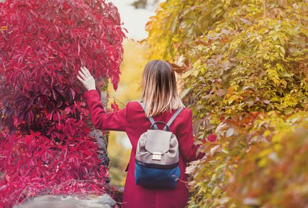 Redhead woman with backpack in garden at autumn season time.