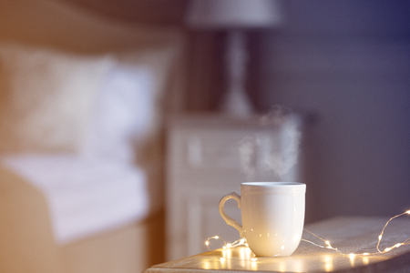 White warm cup of tea of coffee standing on wooden table in bedroom.