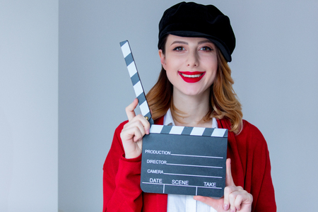 Portrait of young redhead woman in red cardigan and hat with clapboard on grey background. Image made with native lights Stock Photo