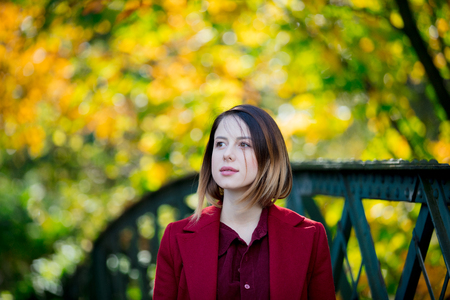 Young redhead woman in red coat have a rest in autum park