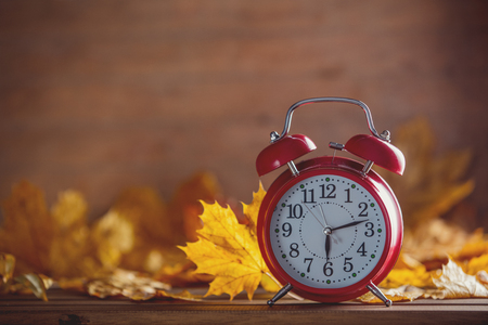 Vintage alarm clock and maple tree leaves on yellow wooden background with bokeh. Autumn season image style Stock Photo