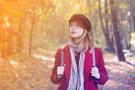 Young redhead woman in red coat and backpack have a rest in autum park