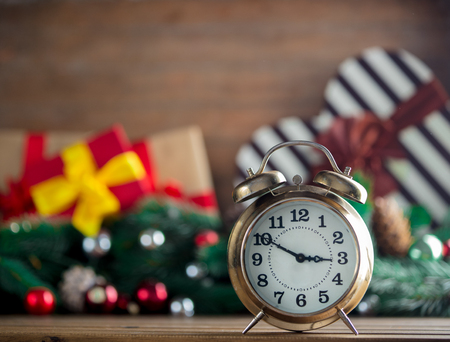 Alarm clock on wooden table with Christmas gifts and pine on background Stock Photo