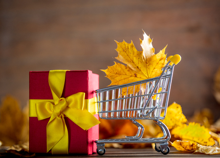 Vintage cart with gift box and maple tree leaves on yellow wooden background with bokeh.