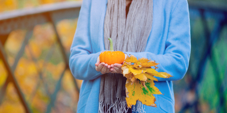 Young redhead woman in blue coat holding yellow maple tree leaves and pumkin in autum park