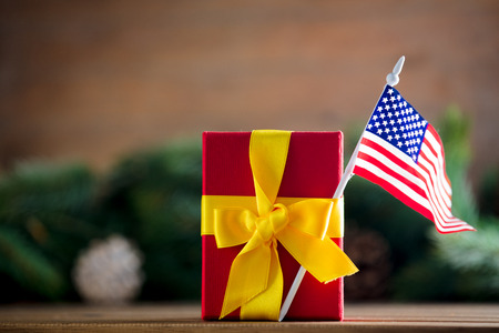 Little gift box with United States of America flag and pine cones and branches on background. Stock Photo