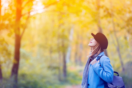 Young redhead woman in blue coat and backpack have a rest in autum park