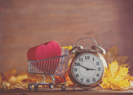 Vintage alarm clock and maple tree leaves with gift box present in shopping cart on yellow wooden background with bokeh.