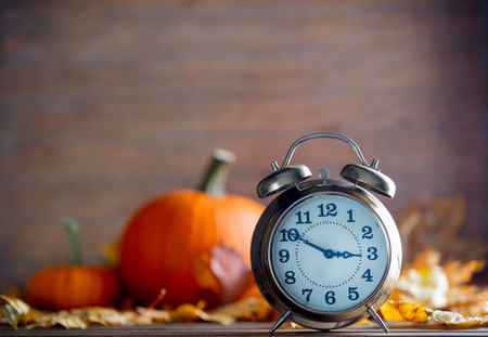 Vintage alarm clock and maple tree leaves with pumpkins on yellow wooden background with bokeh.