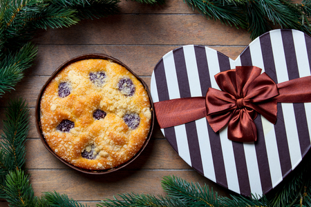 Christmas pie and gift boxes around on wooden table. Hight angle point of view