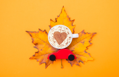 cup of cappuccino with heart shape and toy car on maple leaf. Autumn season image Stock Photo